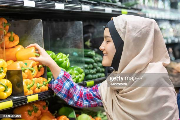 Smiling young muslim woman shopping for vegetables