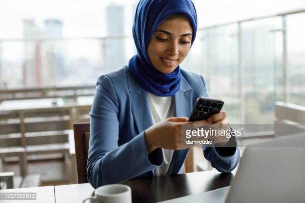 smiling young muslim woman using mobile phone and laptop at a cafe - burka stock pictures, royalty-free photos & images