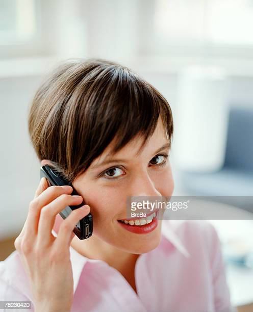 smiling young office worker talking on cellphone