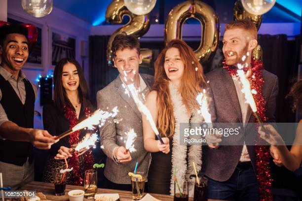 smiling young people holding fireworks - happy new year 2020 stock photos and pictures