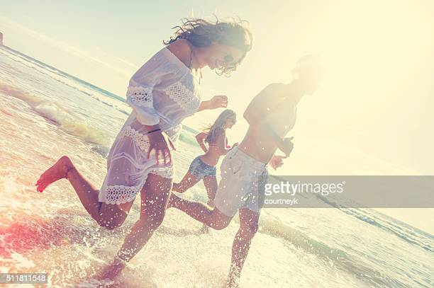 Smiling young people running on the beach