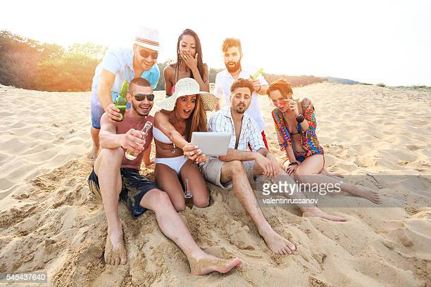Smiling young people sitting on sand and making selfie