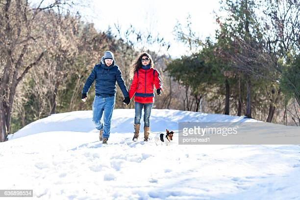 Smiling young people walking with a dog in snow forest