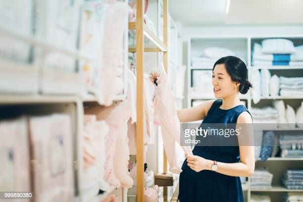 smiling young pregnant woman shopping for baby clothes in shop - maternity wear stock pictures, royalty-free photos & images