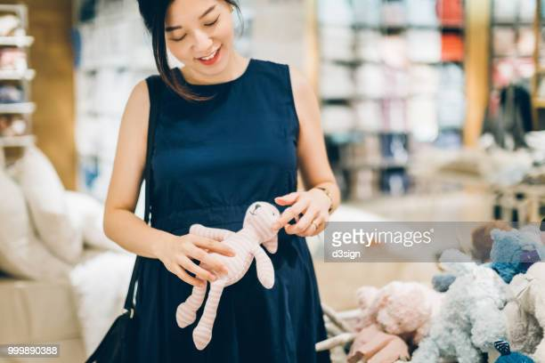 smiling young pregnant woman shopping for baby soft toys in shop - maternity wear stock pictures, royalty-free photos & images