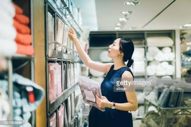 smiling young pregnant woman shopping for home necessities in shop - bedclothes stock pictures, royalty-free photos & images