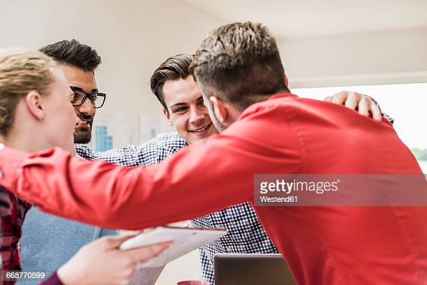 Smiling young professionals embracing in office