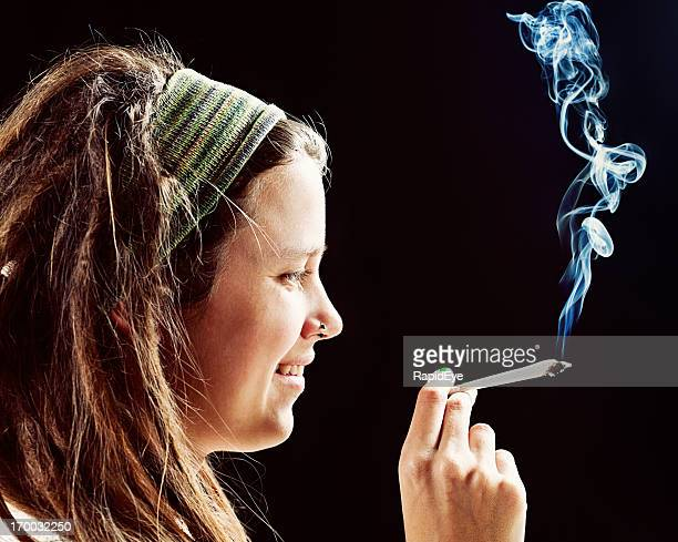 Smiling young rasta girl holds hand-rolled reefer