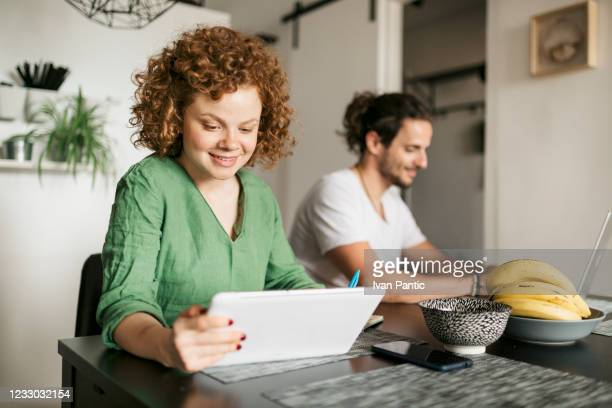 smiling young redhead woman working at home - ginger banks stock pictures, royalty-free photos & images