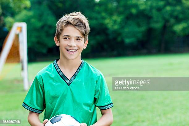 Smiling young soccer player holding onto the ball