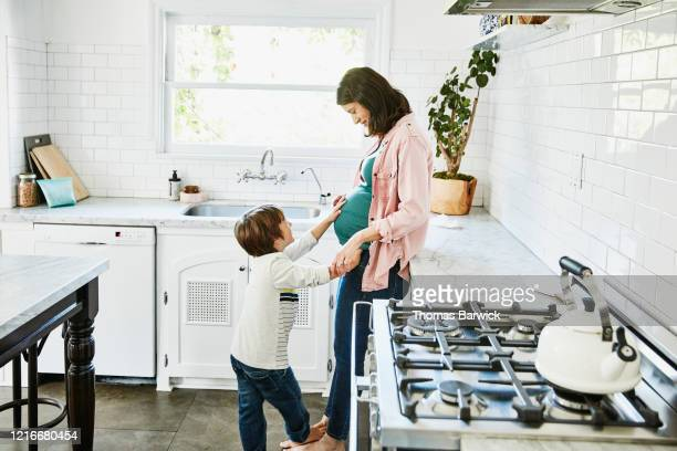 smiling young son putting hand on pregnant mothers stomach while standing in home kitchen - barefoot stock pictures, royalty-free photos & images