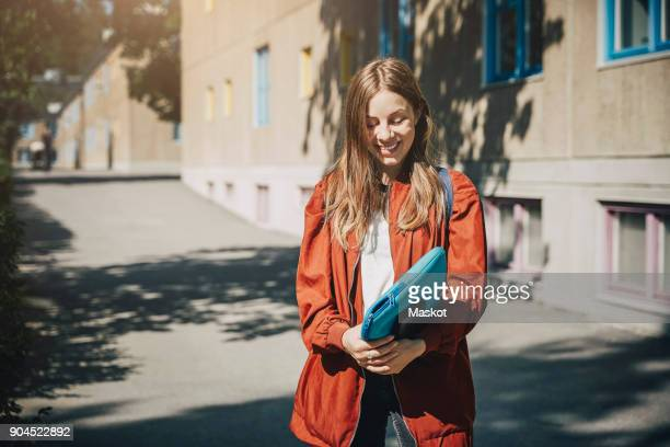 smiling young student holding folder while standing on road in university campus - campus stock-fotos und bilder