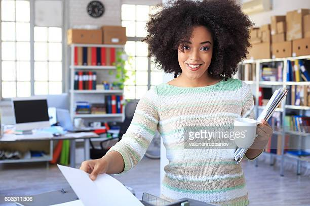 Smiling young student using copy machine