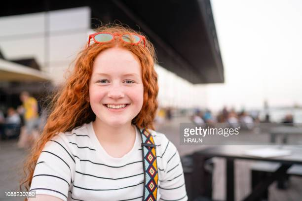 smiling young teenage girl with long red hair. - 12 13 anni foto e immagini stock