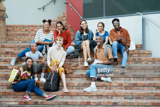 smiling young university students sitting on steps - generation z stock pictures, royalty-free photos & images