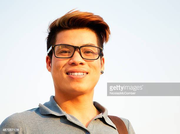 Smiling young Vietnamese male student wearing glasses