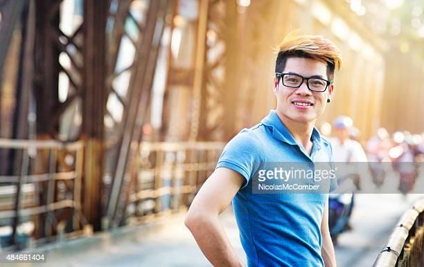 Smiling young Vietnamese man on Long Bien bridge turning