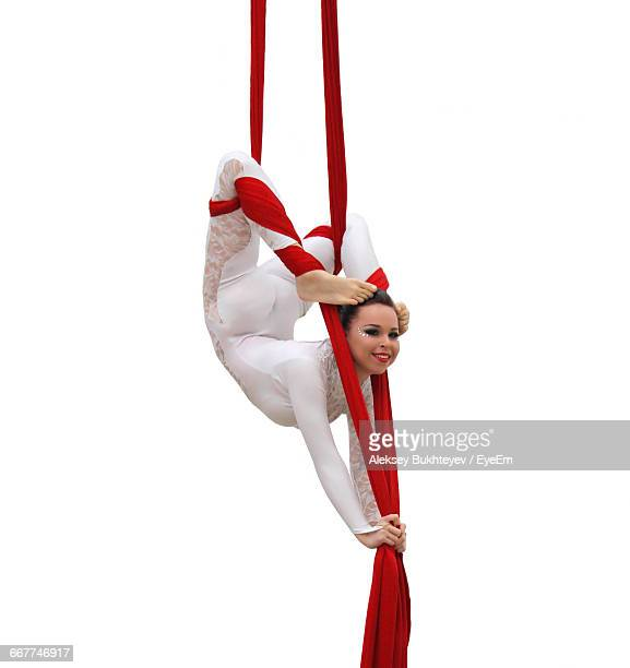 Smiling Young Woman Acrobat Performing With Silk Ropes Against White Background