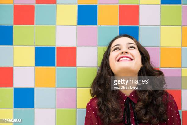 Smiling Young Woman Against Colorful Wall