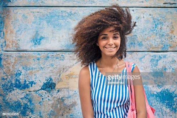 smiling young woman against weathered blue wall - sleeveless stock photos and pictures