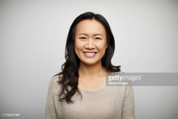 smiling young woman against white background - asien stock-fotos und bilder