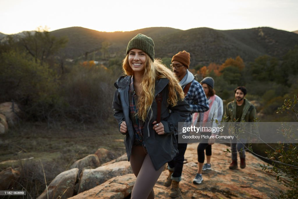 Smiling young woman and friends hiking up a hill together : Stock Photo