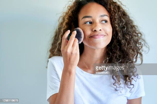 smiling young woman applying face powder with make-up brush against white wall - applying stock pictures, royalty-free photos & images