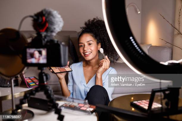 smiling young woman applying make-up while being filmed in camera - filming stock pictures, royalty-free photos & images