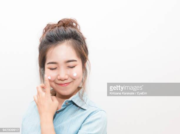 Smiling Young Woman Applying Moisturizer Against White Background