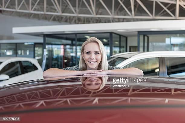 Smiling young woman at car dealership