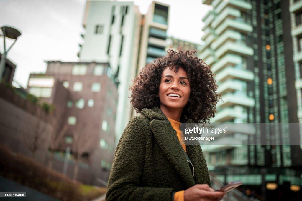 Une jeune femme de sourire au secteur du centre-ville : Photo