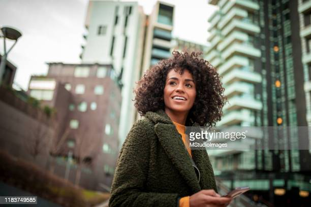 a smiling young woman at the downtown district - black jacket stock pictures, royalty-free photos & images