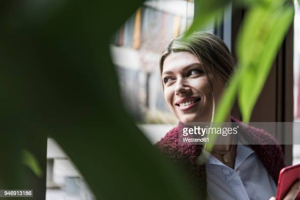 smiling young woman at the window - variable schärfentiefe stock-fotos und bilder