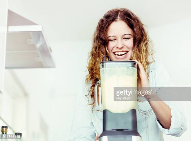 Smiling young woman busy in kitchen with blender, making smoothie