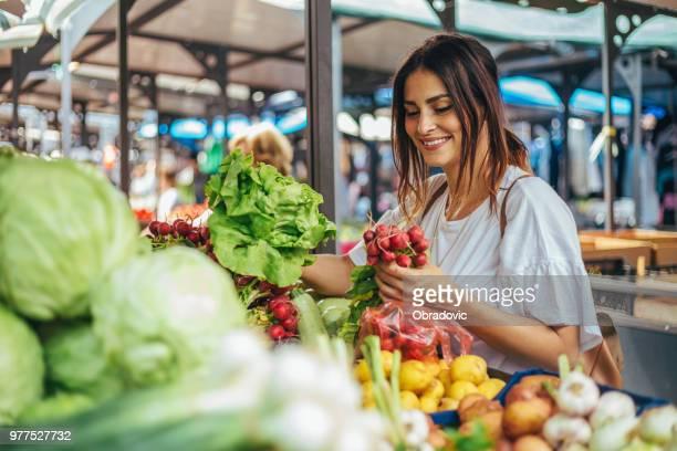 Lächelnde junge Frau Radieschen auf dem Grünen Markt zu kaufen