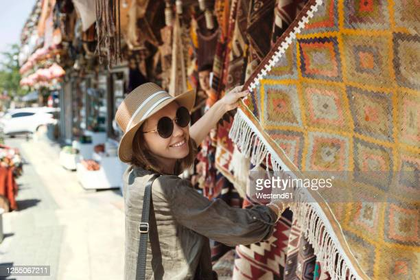 smiling young woman buying shawl at market stall in goreme, cappadocia, turkey - ネヴシェヒル県 ストックフォトと画像