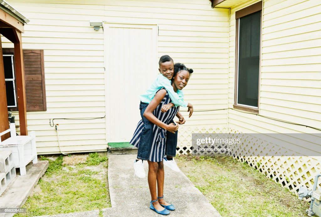 Smiling young woman carrying younger brother on back : Stock Photo