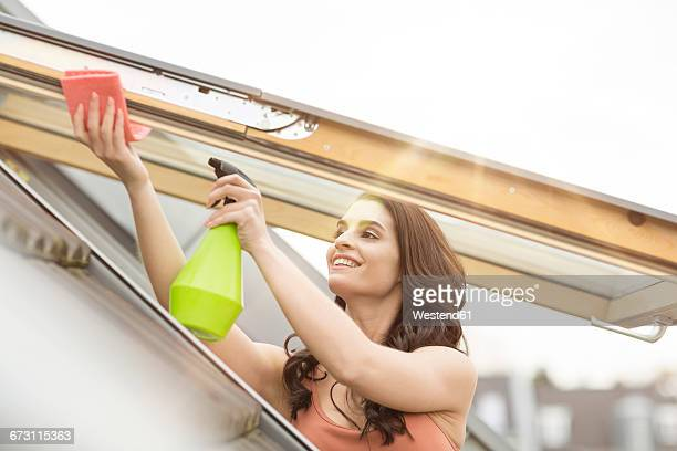 Smiling young woman cleaning roof window