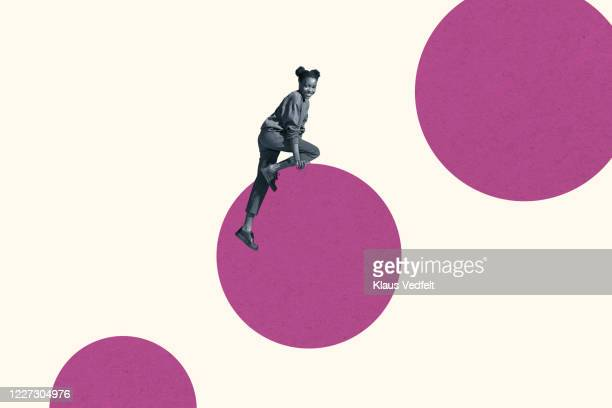 smiling young woman climbing on magenta circle - mountaineering stock pictures, royalty-free photos & images