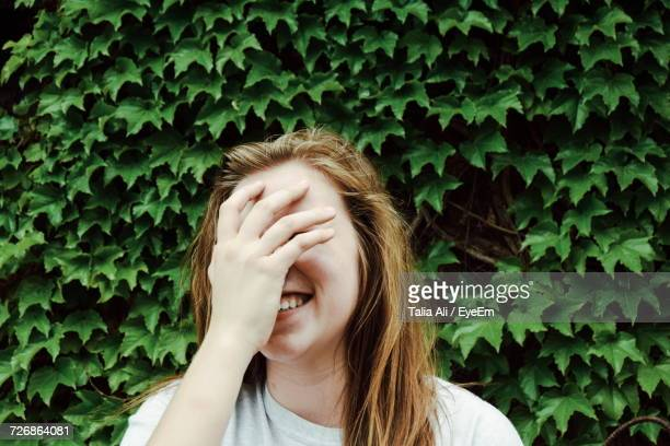 Smiling Young Woman Covering Face While Standing Against Plants