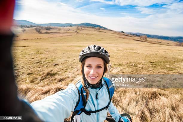 sonriente mujer joven cycler fondo selfie - cross country cycling fotografías e imágenes de stock