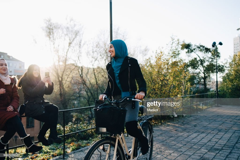Smiling young woman cycling on footpath by female friends sitting on railing in city : Stock Photo