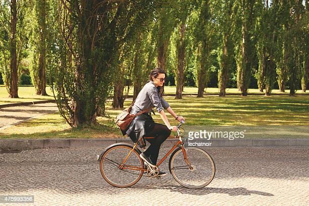 sonriente mujer joven ciclismo en el parque de la ciudad - cabello castaño fotografías e imágenes de stock