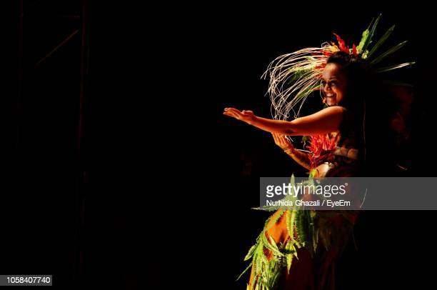 smiling young woman dancing against black background - tahiti stock pictures, royalty-free photos & images