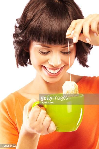 Sonriente Joven mujer Dipping bolsa de té en una taza