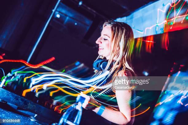 Smiling Young Woman DJ Performing in Nightclub
