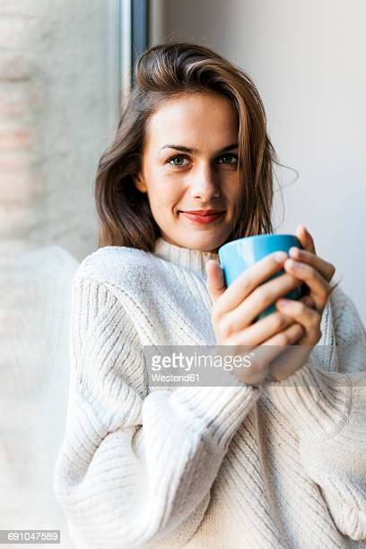 smiling young woman drinking a coffee at a window - hot spanish women stock pictures, royalty-free photos & images