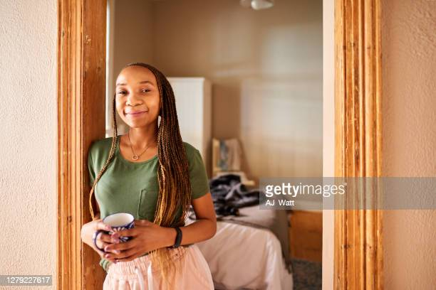 smiling young woman drinking a coffee at her bedroom door - doorway stock pictures, royalty-free photos & images