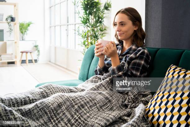 smiling young woman drinking coffee while relaxing on sofa at home - resting stock pictures, royalty-free photos & images