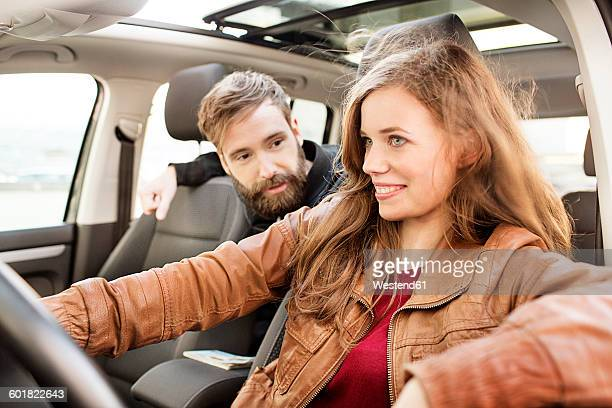 smiling young woman driving car with man on backseat - casal heterossexual imagens e fotografias de stock